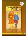 En mor i brun rock och hennes barn i blå jacka går på en trottoar. Brunt omslag.