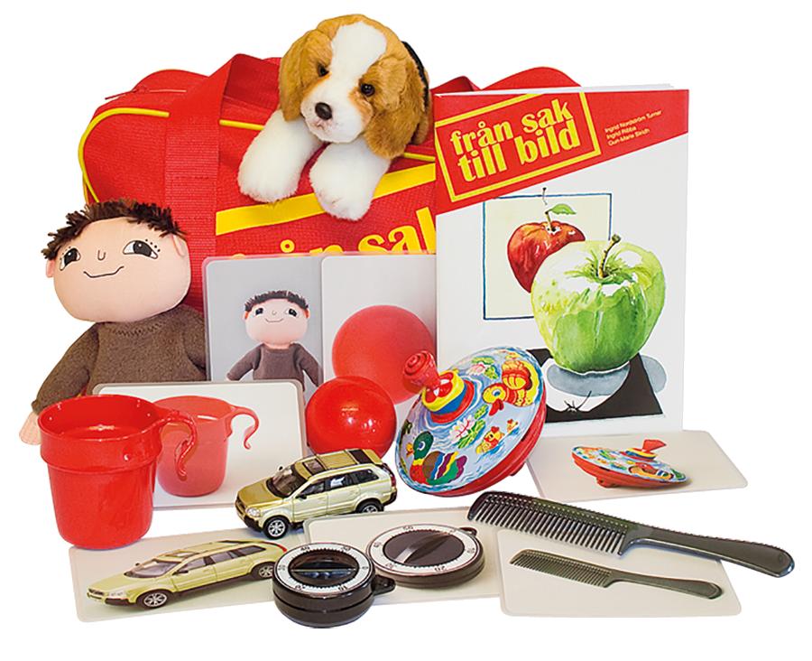 En röd väska med två dockor bredvid, en i form av en hund och en annan av Alfons Åberg. Diverse föremål i förgrunden, såsom en mugg och en leksaksbil.